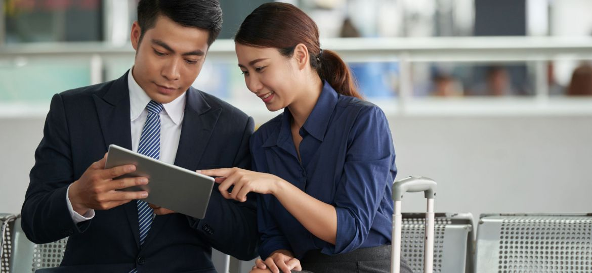 Asian Couple Using Tablet in Airport