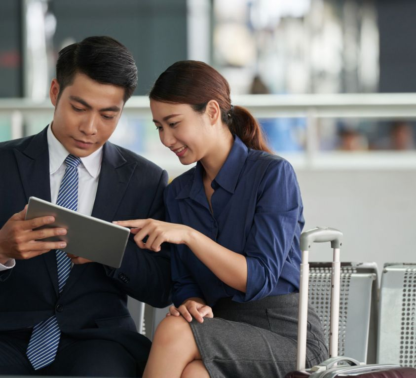 Portrait of two Asian business people, man and woman, using digital tablet while waiting in airport departure zone travelling on business trip