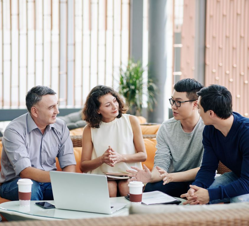 Business people looking at colleague sharing creative ideas at meeting